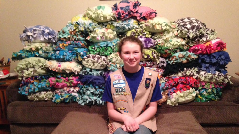 """Gabrielle Bruns, a member of Girl Scout Troop No. 140 of Buxton, with the 64 pillows that were created for a """"Pillows for Patients"""" campaign she oversaw as part of a scouts community service project."""