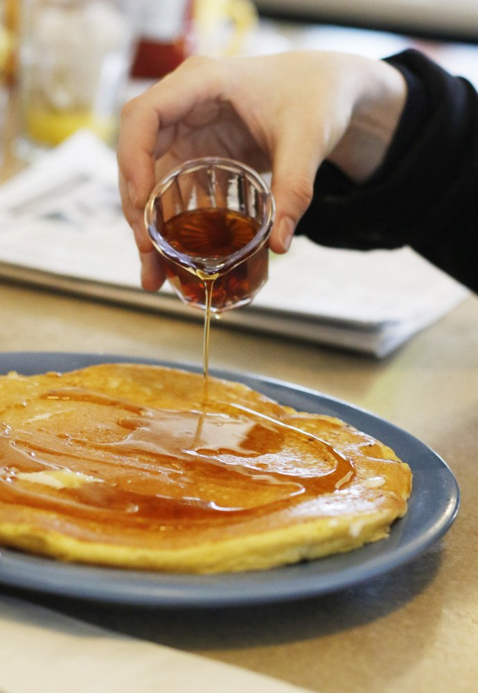PORTLAND, ME - MARCH 13: A customer pours pure Grade A maple syrup on her pancake at the Miss Portland Diner. (Photo by Jill Brady/Staff Photographer)