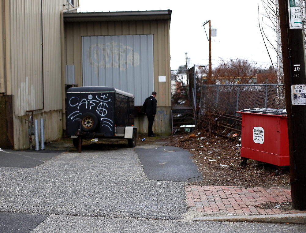 A police detective searches a loading dock area next to the building where police say a shooting happened late Tuesday night.