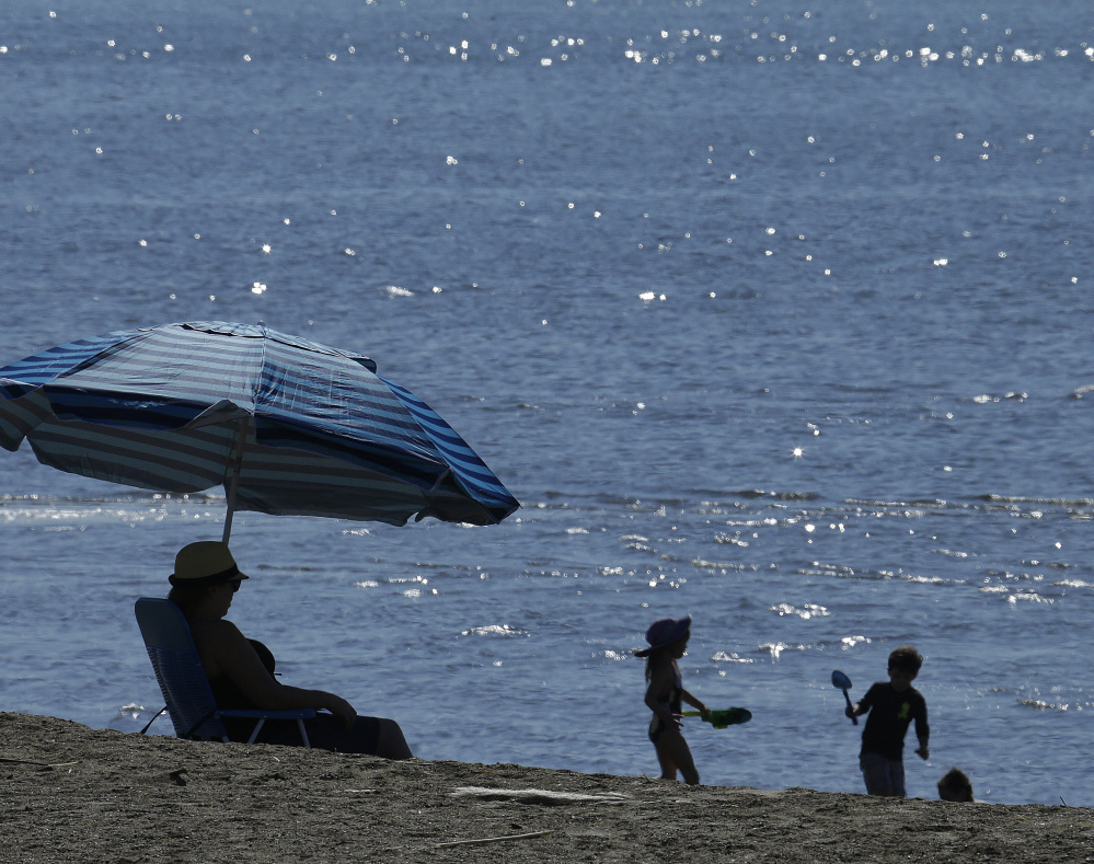 Unseasonably warm temperatures bring out an early crowd at Crown Beach, Calif., Tuesday, as a mild West Coast winter nears its end.
