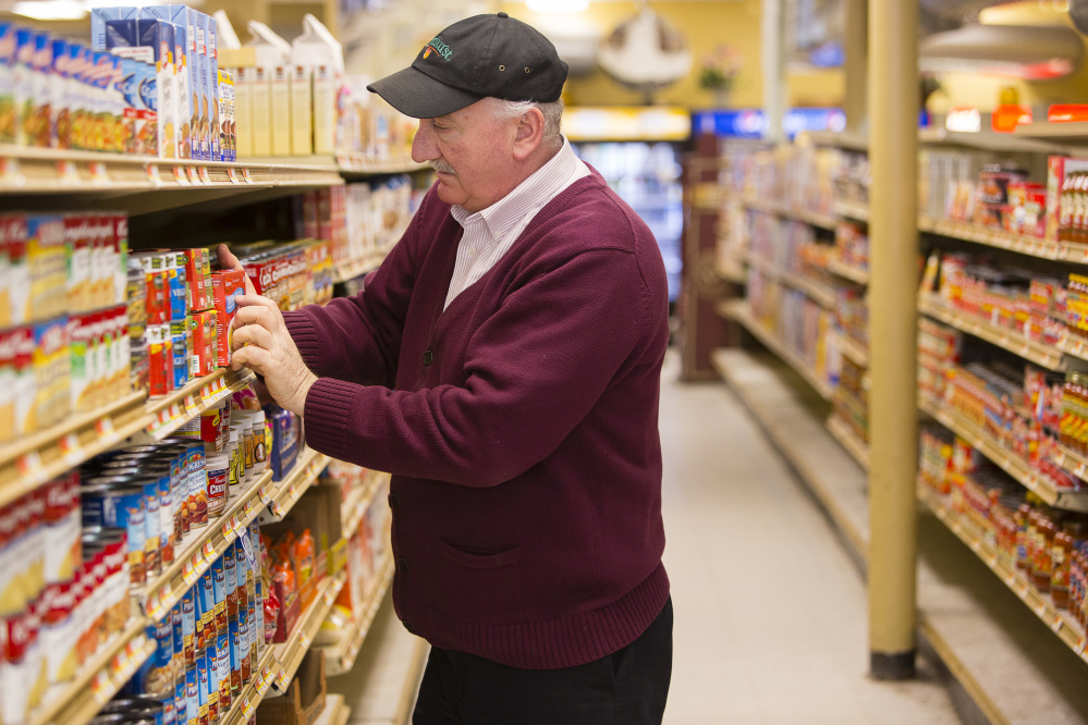 Paul's Food Center owner Jim Trusiani stocks shelves in the Congress Street market Friday. Carl D. Walsh/Staff Photographer