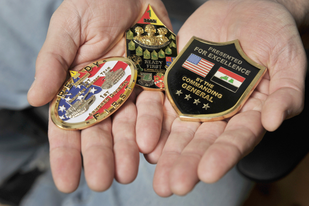 "Roberts displays the ""challenge coins"" he acquired while in the Army."