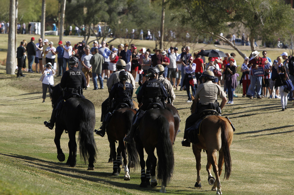 An Arizona police mounted unit patrols outside a Donald Trump campaign rally in Fountain Hills as supporters line up. Below, Alex Renner washes his eyes with bottled water at the scene of a protest against Trump on Saturday.