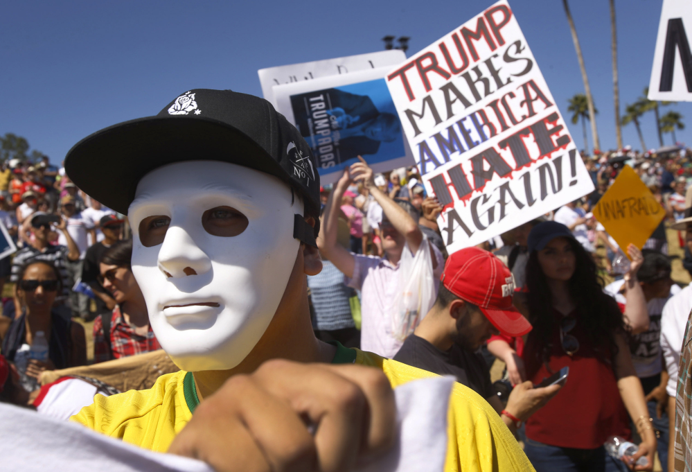 Protesters against Republican presidential candidate Donald Trump appear at a rally for Trump in Fountain Hills, Ariz., on Saturday.