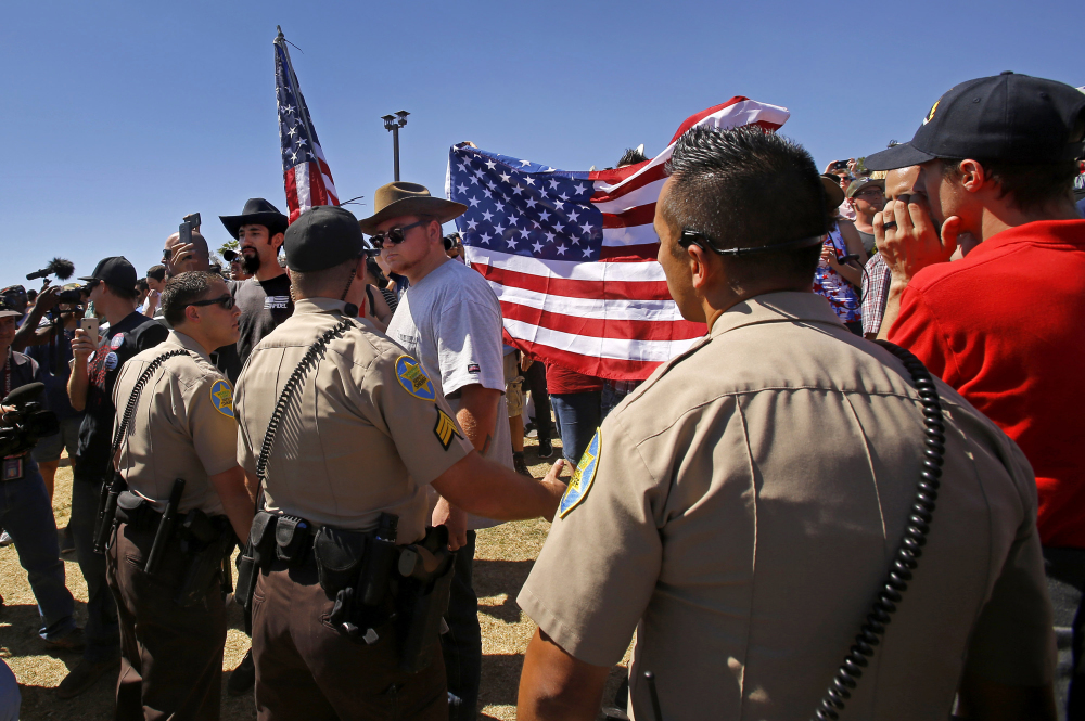 Sheriff's deputies form a barrier between supporters and protesters that came to see Republican presidential candidate Donald Trump in Fountain Hills, Ariz., on Saturday.
