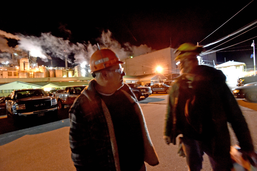 Doug Mathieu, left, says goodbye to a co-worker in November in the parking lot after his final shift at the Androscoggin Mill in Jay.
