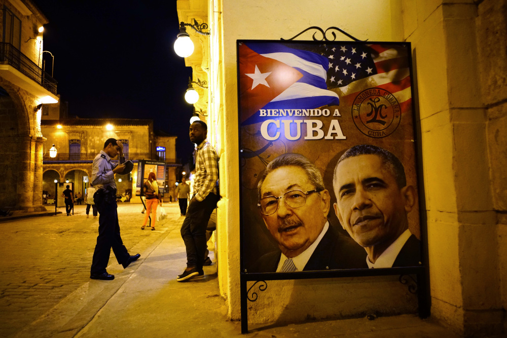 In Havana, a welcome poster features images of Cuba's President Raul Castro and President Obama, as Obama becomes the first sitting U.S. president to visit in 90 years.