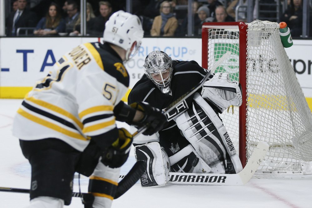 Los Angeles Kings goalie Jonathan Quick, right, makes a save on a shot by Boston Bruins center Ryan Spooner, left, during the third period Saturday in Los Angeles.