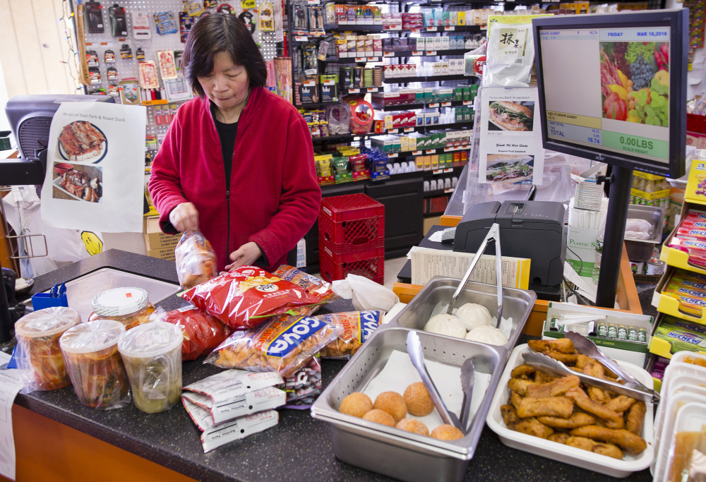 Cashier Mei Lam rings up a customer's purchase at Veranda Asian Market on Forest Avenue in Portland.