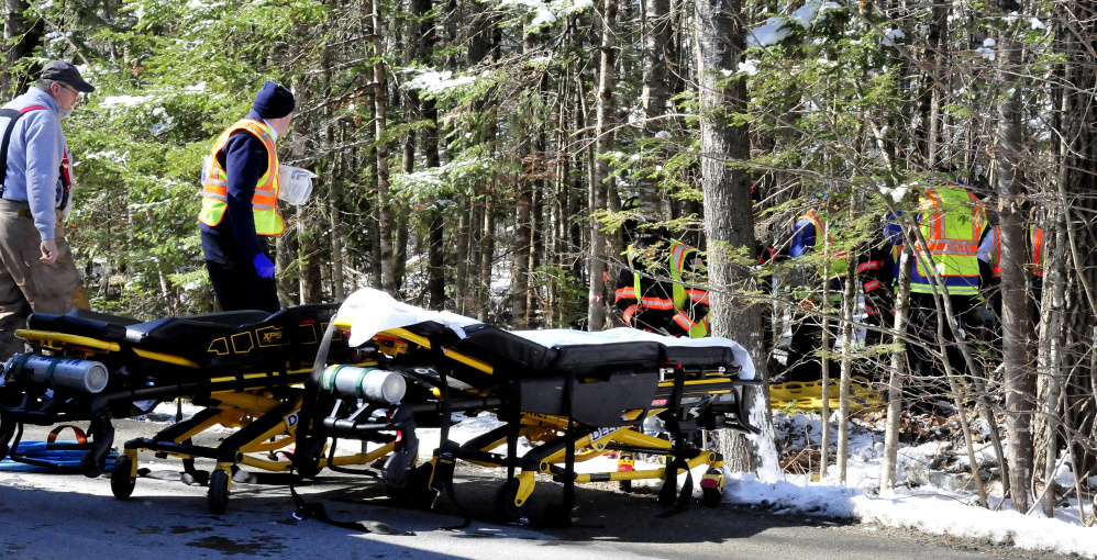 Firefighters wait beside gurneys as other firefighters free three victims from the wreckage of a car that landed in the woods Tuesday off Hanscom Road in Benton.