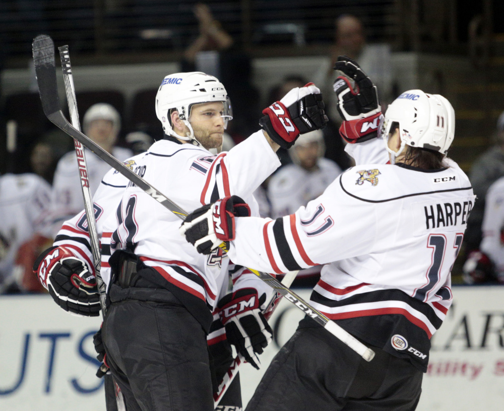 Rob Schremp of the Portland Pirates celebrates with teammate Shane Harper, right, after scoring in the second period of a 6-3 win over Bridgeport on Wednesday night at the Cross Insurance Arena in Portland.