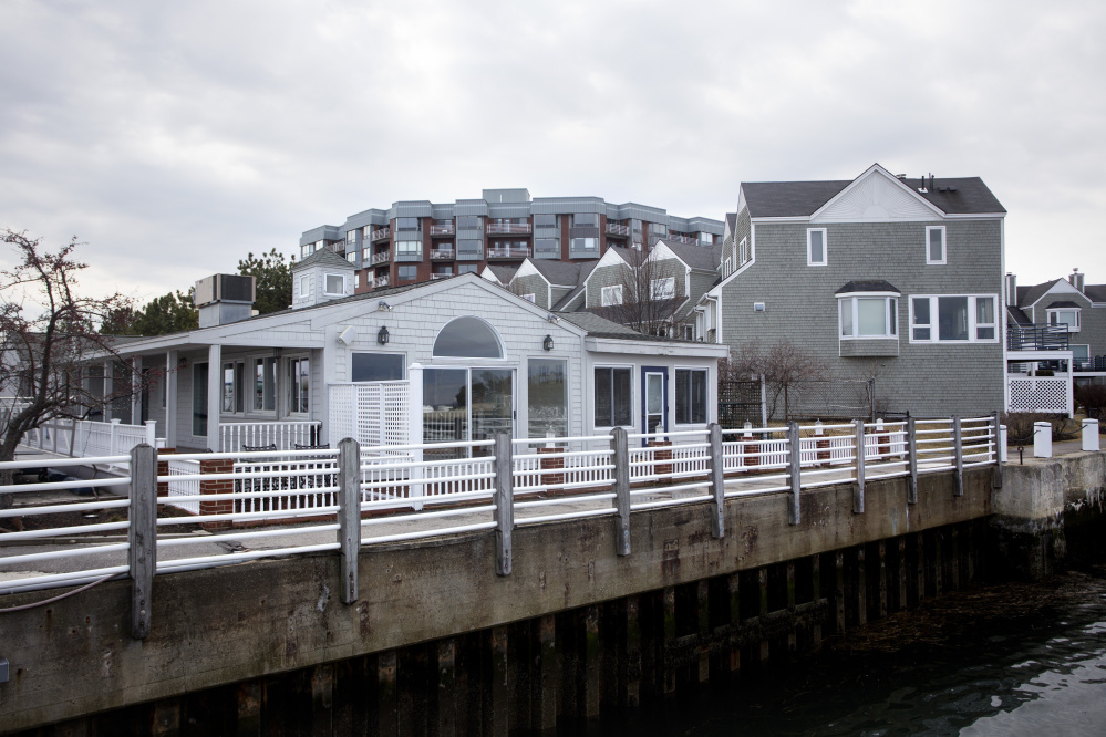 City councilors approved a proposal this week for a new upscale restaurant to replace the former Joe's Boathouse, left, next to the Breakwater condominiums in South Portland. The project faces additional review hurdles.