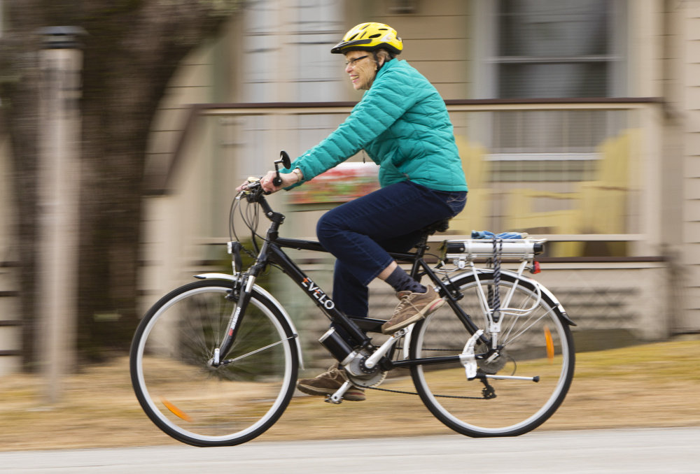 Melchiskey rides her motorized bicycle near her home in Camden. She still pedals, and usually uses the motor on its lowest setting unless she needs a boost to get up a hill.