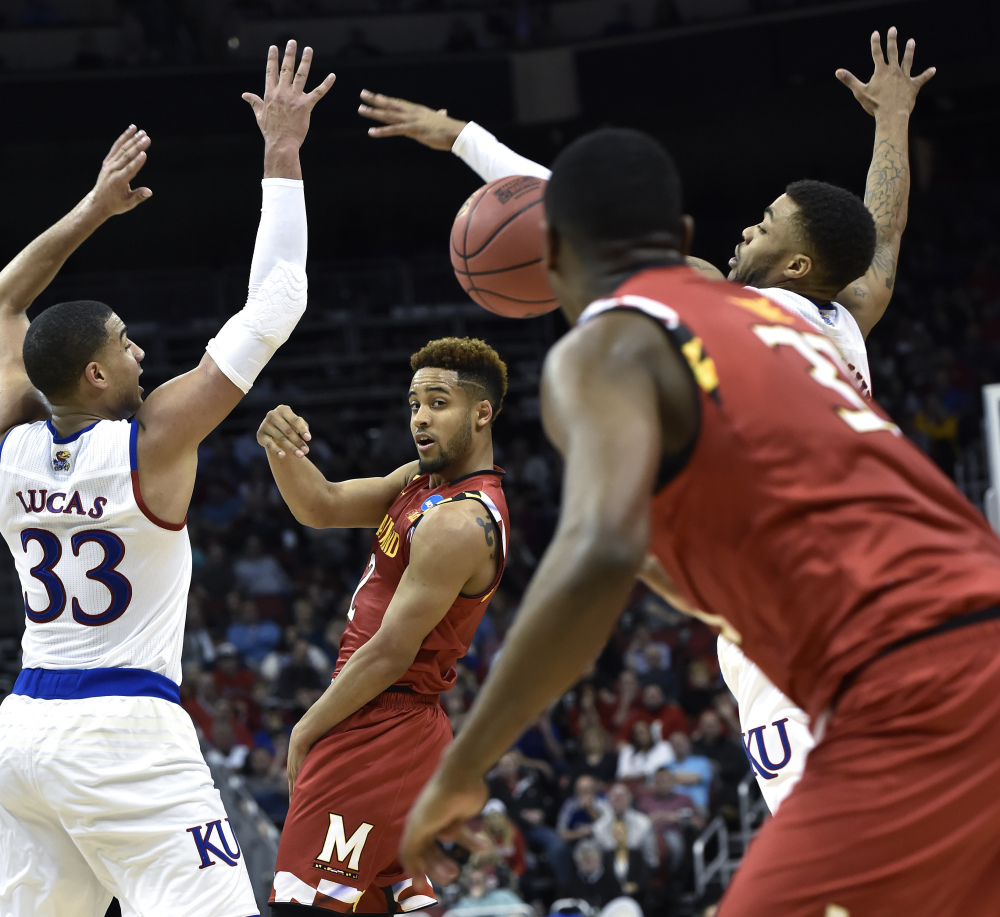 Maryland guard Melo Trimble passes the ball to a teammate between Kansas forward Landen Lucas (33) and guard Wayne Selden Jr. in the first half.
