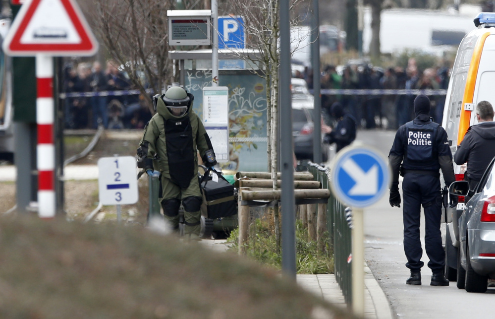 A police officer wears a bomb suit in Brussels during a day of police raids and investigations. A tram passing through the area was stopped and evacuated and police cordoned off a wide perimeter of streets.