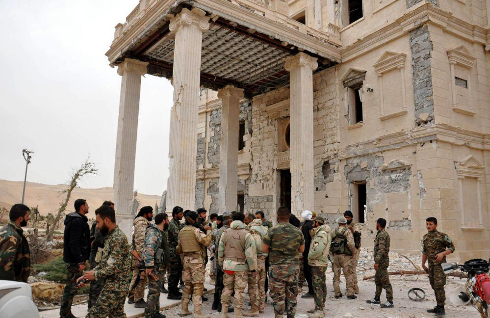 In this photo released on March 24, 2016, by the Syrian official news agency SANA, Syrian government soldiers gather outside a damaged palace, in Palmyra, central Syria.