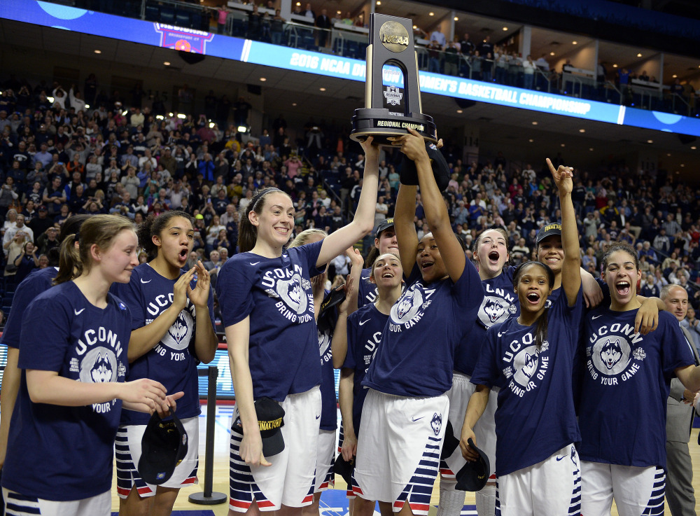 Connecticut's Breanna Stewart, left, and Morgan Tuck celebrate with the trophy and teammates after winning 86-65 over Texas in their regional final Monday night in Bridgeport, Conn.