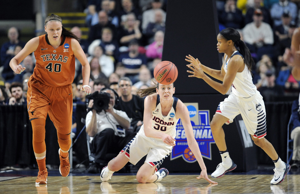 Breanna Stewart flips the ball to Moriah Jefferson, right, to start a fast break as Texas' Kelsey Lang pursues in the first half of Monday night's win by the Huskies.