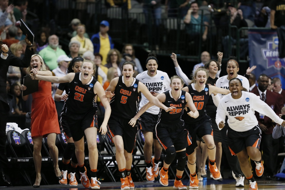 Oregon State players rush the court celebrating their 60-57 win over Baylor in Monday night's regional final in Dallas. Oregon State is headed to the Final Four for the first time.