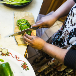 PORTLAND, ME - MARCH 9: Pascaline Lisembe chops green pepper as she prepares cassava, which is one of her husband's favorite dishes at her home in Portland, ME on Wednesday, March 9, 2016. (Photo by Whitney Hayward/Staff Photographer)