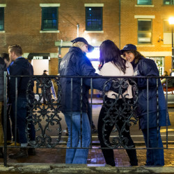 Two street pastors offer aid to a woman in the Old Port last Friday. Dozens of members of five local churches have volunteered to spend one Friday night a month on the streets to greet and help people.