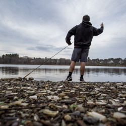 """Teddy Lyman, 20, a junior at Bowdoin College, fly fishes in the Androscoggin River in Brunswick on Thursday. """"This is the first time I've been down here this year,"""" said Lyman, who likes to take a break from studying to be outdoors. Thursday's warmth is expected to give way to colder air."""