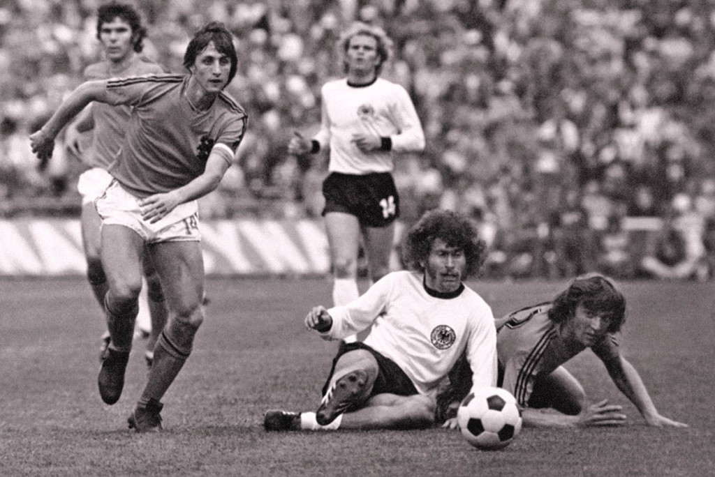 """Dutch forward Johan Cruyff, left, runs past German defender Paul Breitner, sitting on the pitch, during the final of the Soccer World Cup at the Olympic Stadium in Munich, Germany, in this July 7, 1974, photo. Cruyff revolutionized the game with the concept of """"Total Football."""" The Associated Press"""