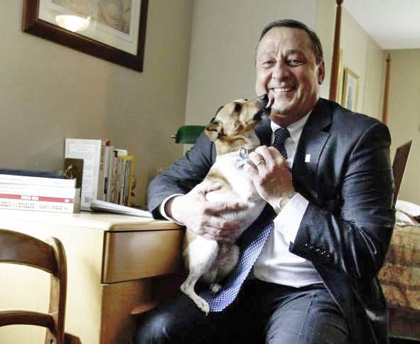 Gov. Paul LePage gets a dog kiss from Baxter, the family's Jack Russell terrier mix that died Tuesday.