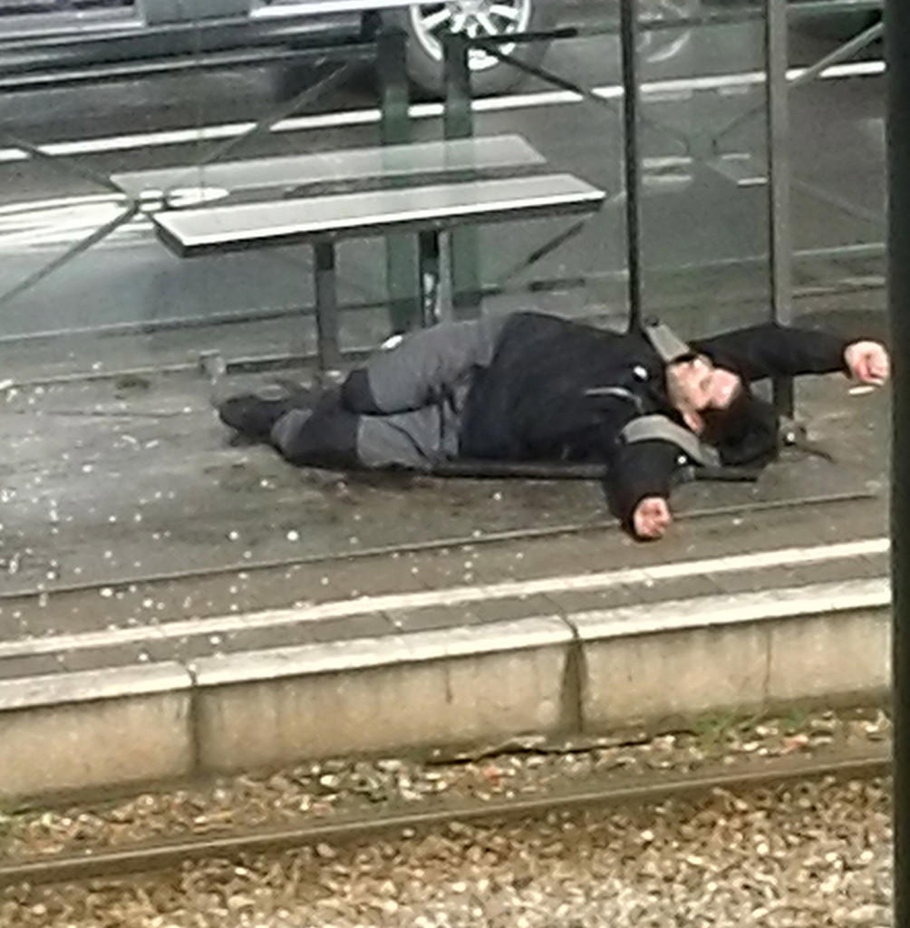 A man lies on the platform at a tram stop in Brussels, Belgium, on Friday, after being injured during a police raid.