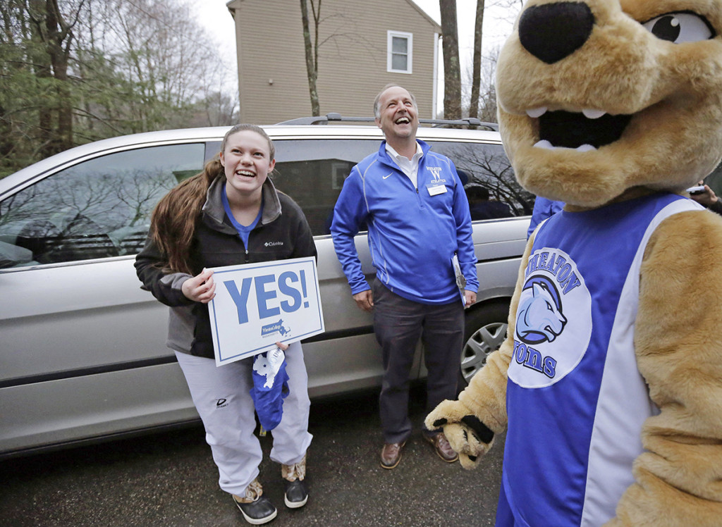Maya Wolf, 17, holds a sign to her mother, not shown, from the driveway of their home in Franklin, Mass., during a  visit by Wheaton College President Dennis Hanno, center, and the school's mascot. The Associated Press