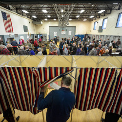 Frank Butler, of Dummerston, Vt., enters the voting booth while members of the community participate in a town hall-style meeting at the Dummerston School's gymnasium on Tuesday.