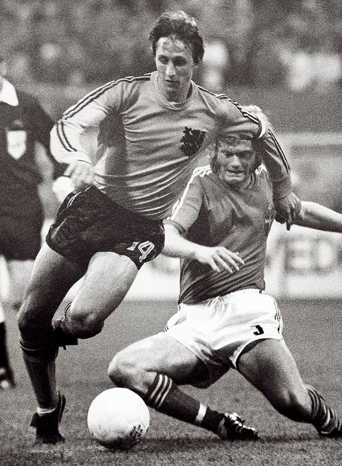 In this June 19, 1974, photo, Johan Cruyff, left, dodges a tackle attempt from Sweden's Kent Karlsson during a World Cup soccer match  in Dortmund, Germany. The Associated Press