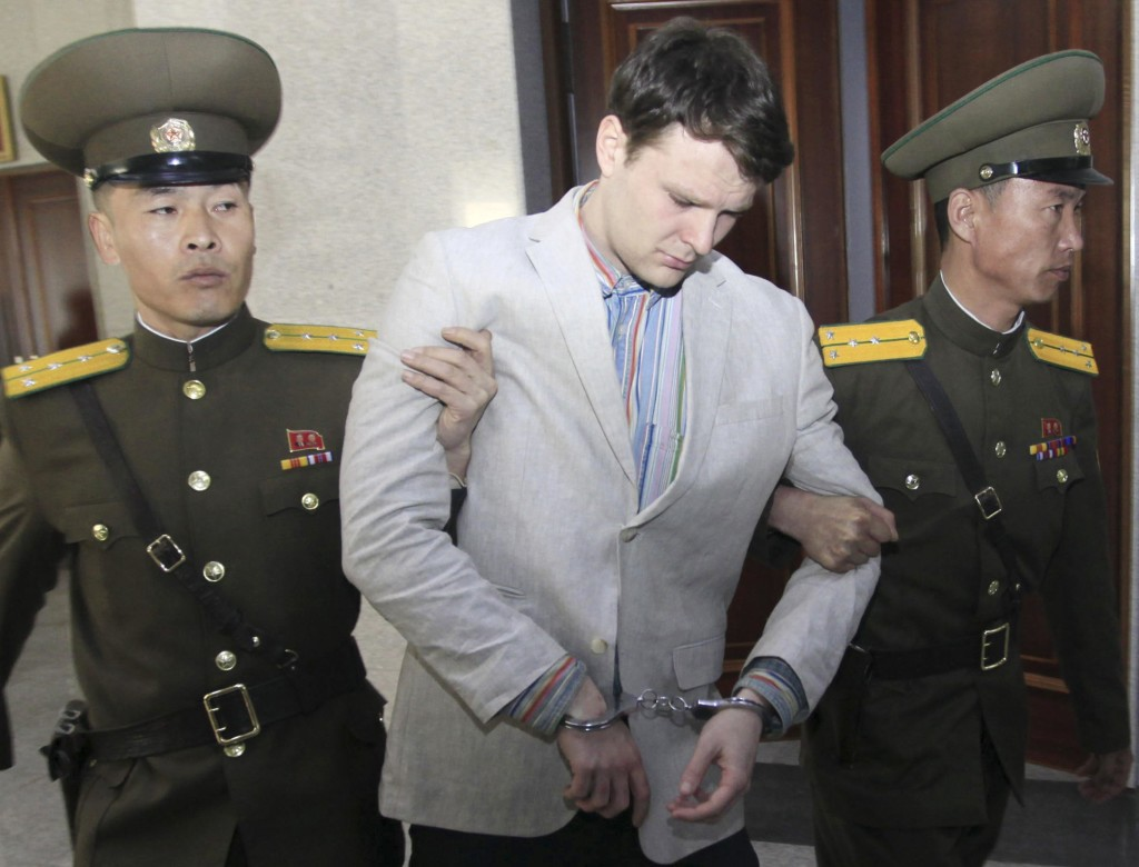 Otto Warmbier is escorted by North Korean guards at the Supreme Court in Pyongyang in this March 16, 2016, photo. He allegedly attempted to steal a propaganda banner from his hotel. The Associated Press