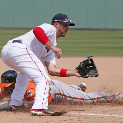 Boston Red Sox third baseman Travis Shaw reaches out for the ball as Baltimore Orioles' Xavier Avery steals third in a spring training gameon Monday in Fort Myers, Fla. The Associated Press