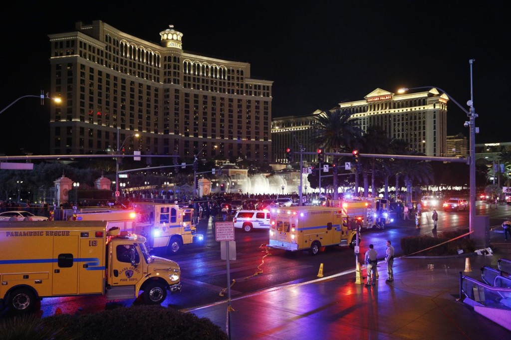 In this Dec. 20, 2015, photo, emergency crews respond to the scene of a car accident along Las Vegas Boulevard in Las Vegas, after a woman drove her car into a crowd of tourists outside the Planet Hollywood and Paris casino-hotels.  The Associated Press