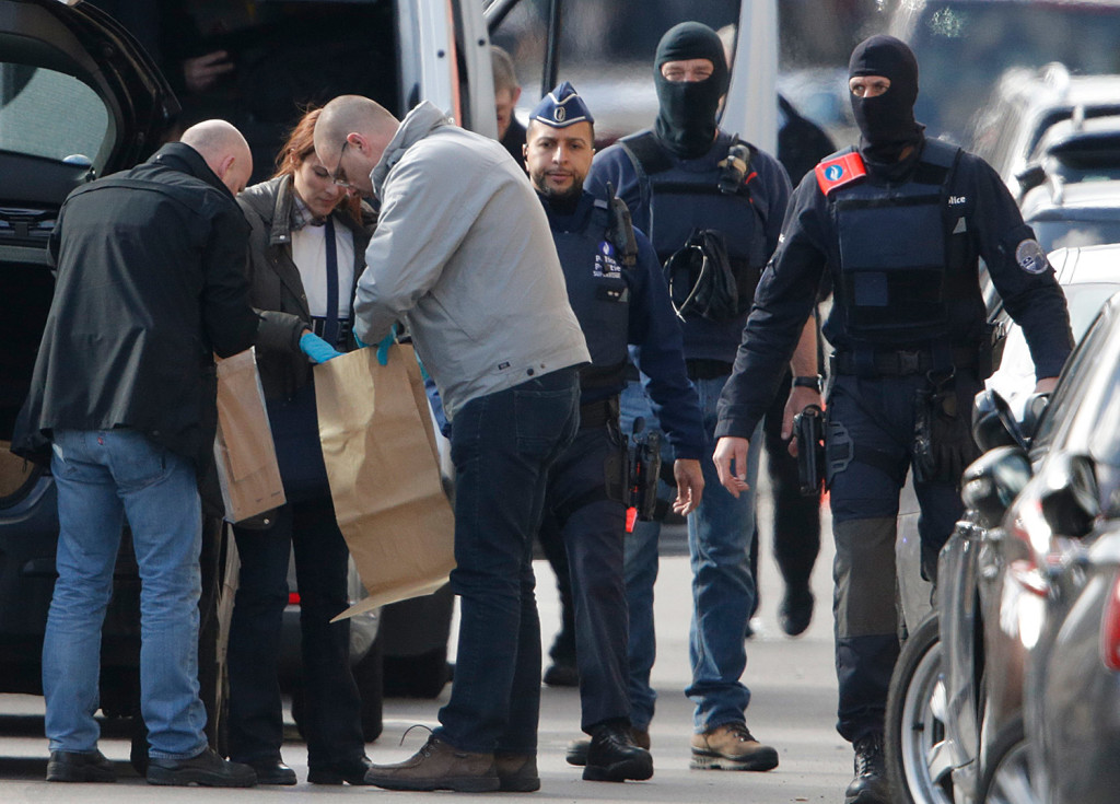 Police look at bags of evidence collected Friday during a search in the Brussels borough of Schaerbeek in connection with Tuesday's bombings in Belgium.