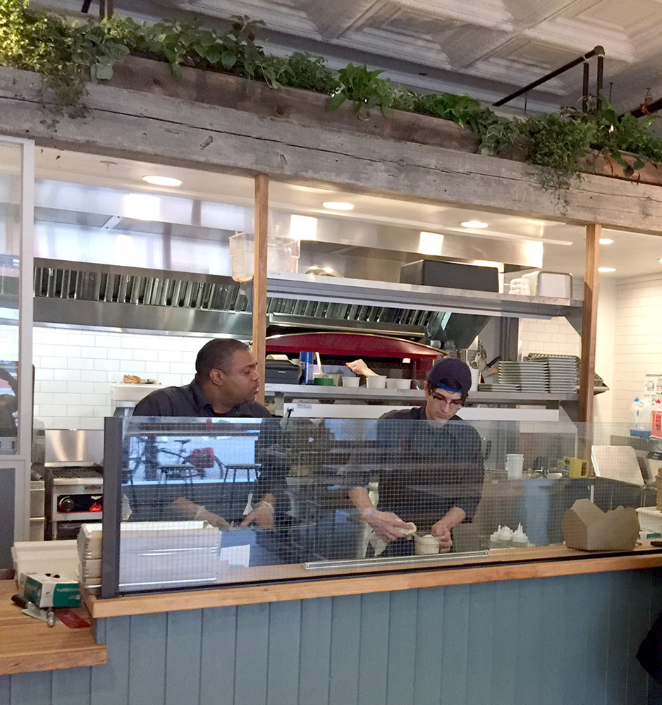 Cooks work behind the counter at Hero in Monument Square.