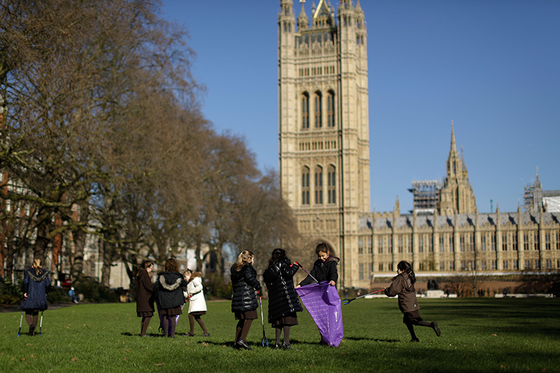 Pupils from Channing School in north London, look for litter as they pose for photographs in Victoria Tower Gardens, next to the Houses of Parliament in London.