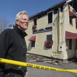 Ed Berg, co-owner of the Corsican Cafe and Chowder House in Freeport, surveys the damage to his building following an early-morning fire.