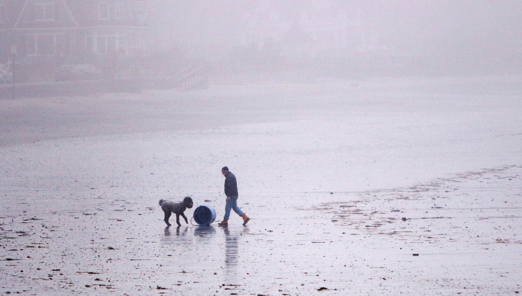 David Jones of Kennebunk rolls a bait barrel up to the sea wall at Gooch's Beach in Kennebunk while walking his dog Fritz at the beach.  The barrel had washed ashore overnight and the high tide at midnight resulted in some splash over that created minor flooding along parts of the coast.