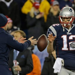 "A football is tossed to Tom Brady during warmups before the AFC Championship game in January 2015, the game that started the ""Deflategate"" case. A federal appeals court ruled Monday that Brady must serve a four-game suspension imposed by the NFL for his role in the underinflation of footballs used in the game."
