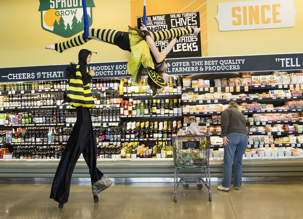 Oscar Tieman, 12 of Pownal, walks on stilts as fellow Circus Maine performer Caroline Odlin, 15 of Brewer, does aerial acrobatics in the beverage section at Whole Foods in Portland on Earth Day, Friday. Carl D. Walsh/Staff Photographer
