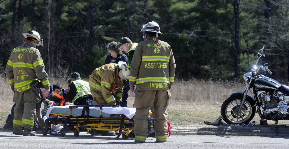 Emergency workers attend to Donald McLeod, 64, of Readfield, who was thrown from a motorcycle Thursday afternoon during an accident on U.S. Route 202 in Manchester.