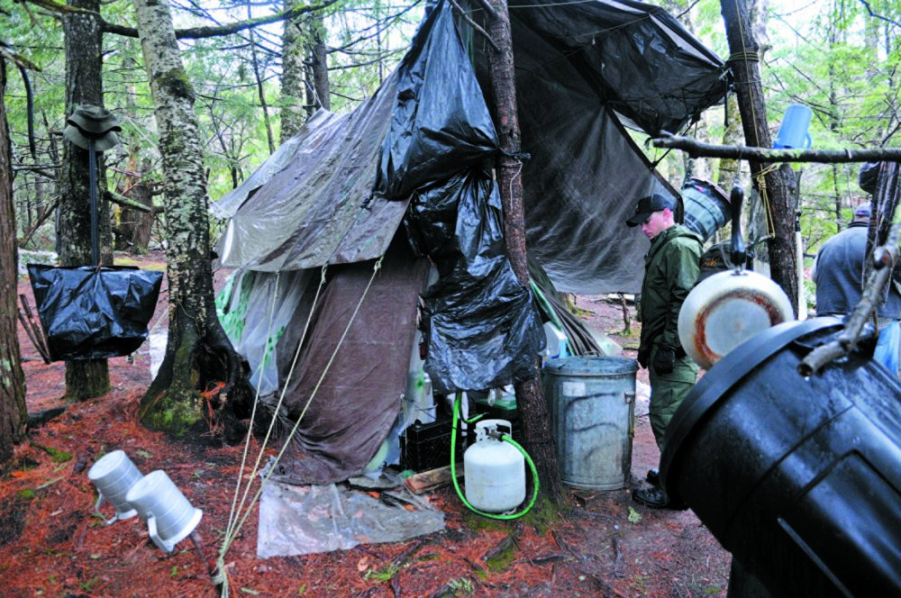 District Game Warden Aaron Cross inspects Christopher Knight's camp in a remote, wooded section of Rome in 2013. Kennebec Journal file photo/Andy Molloy