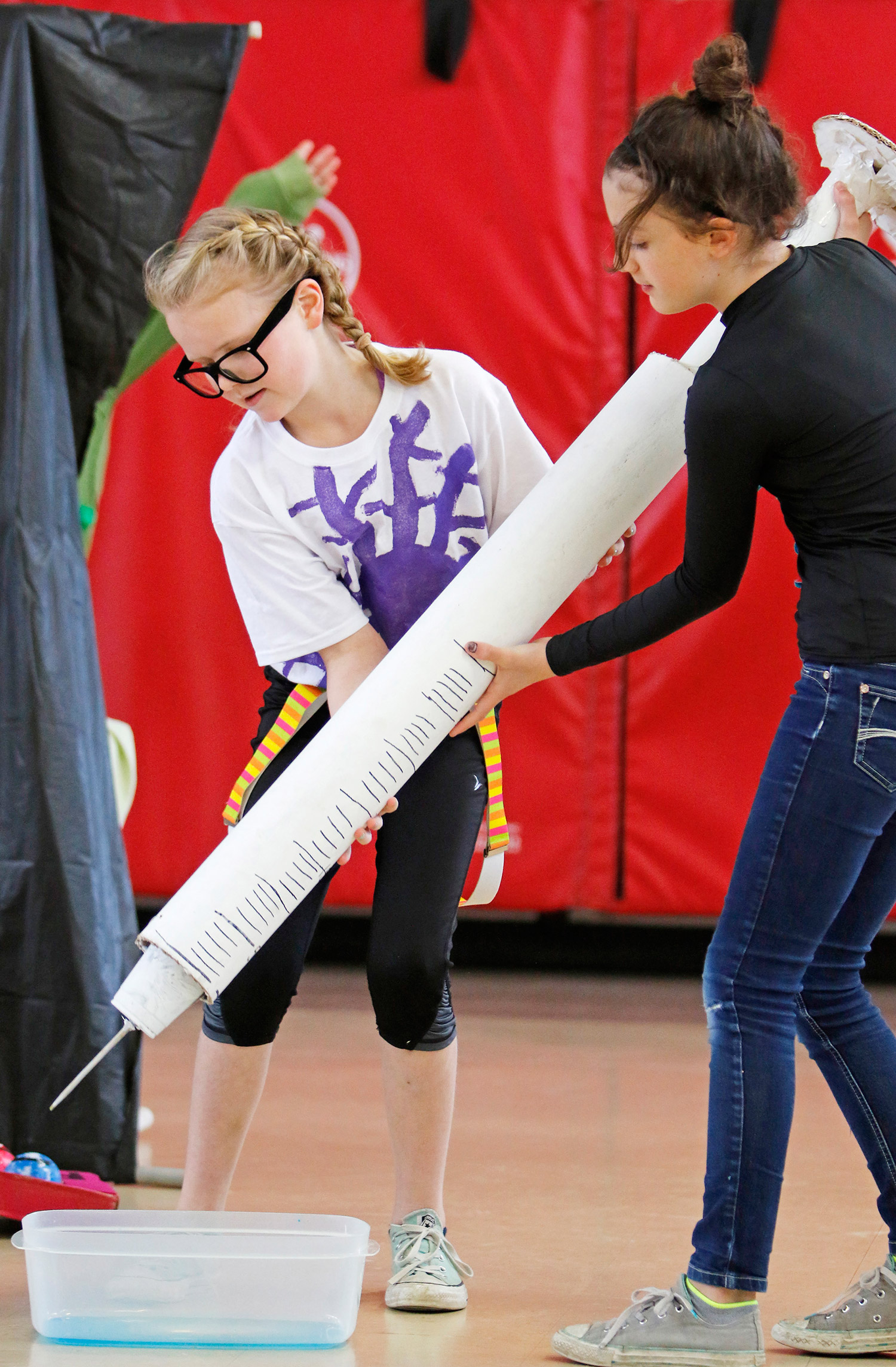"""Lyseth Elementary School fifth graders Emily Seavey and Sammy Desjardins work together to lift a giant syringe during a rehearsal of their team's production """"No-cycle, Recycle"""" that will be performed at the Odyssey of the MInd World Finals in Iowa in May."""