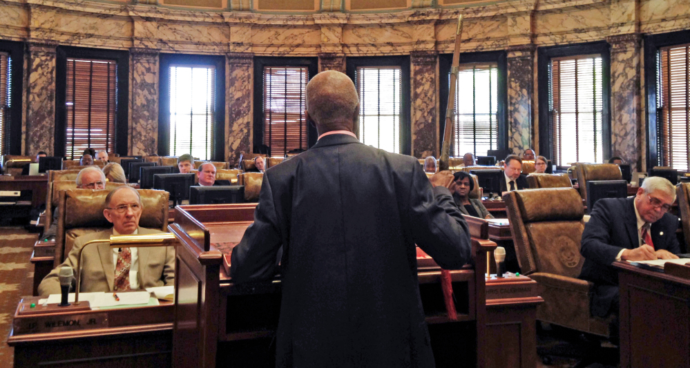 Sen. Hillman Frazier, D-Jackson, brandishes a sheathed sword Tuesday, March 29, 2016, during debate over House Bill 786, at the Capitol in Jackson, Miss. Frazier opposed the bill, which would grant immunity to trained church security teams that shoot people trying to commit violent crimes. Frazier said the bill went against Christian teaching, recounting the story of Jesus healing a servant of a high priest after a disciple cut off the servant's ear with a sword. (AP Photo/Jeff Amy)