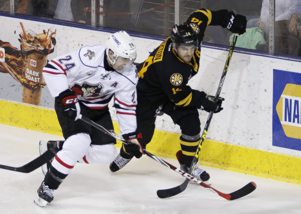 Pirate's Cameron Gaunce, left, and Bruin's Ben Sexton, race for the puck Friday during the second period of their game in Portland, Maine. Joel Page/Staff Photographer