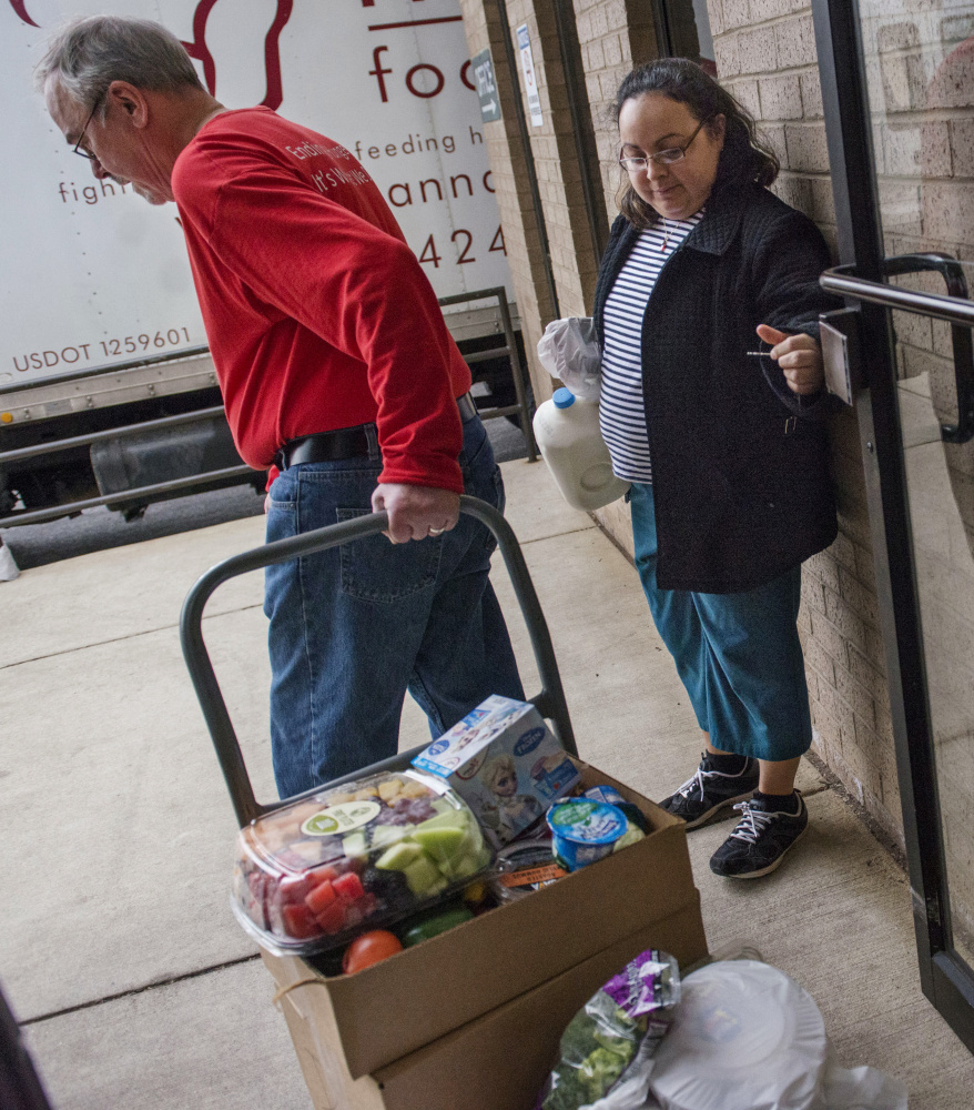 Rosalba Diaz holds the door for Dean Swanson on Thursday at the Manna Food Center in Gaithersburg, Md. As of Friday, recipients of food stamps in 22 states faced a work mandate.