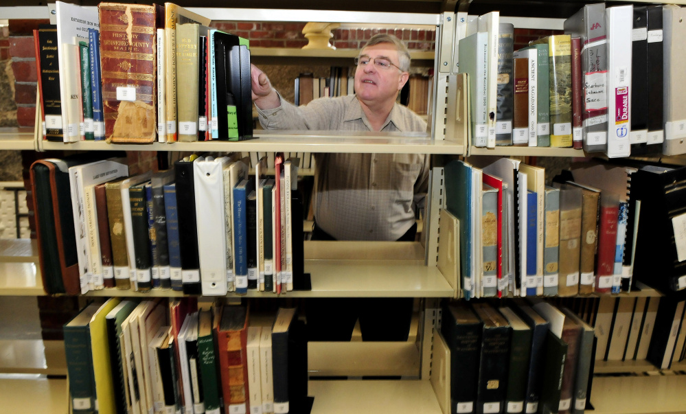 Dale Jandreau, librarian at Skowhegan Free Public Library, selects a book of documents on area families Wednesday in the library's new genealogy section.