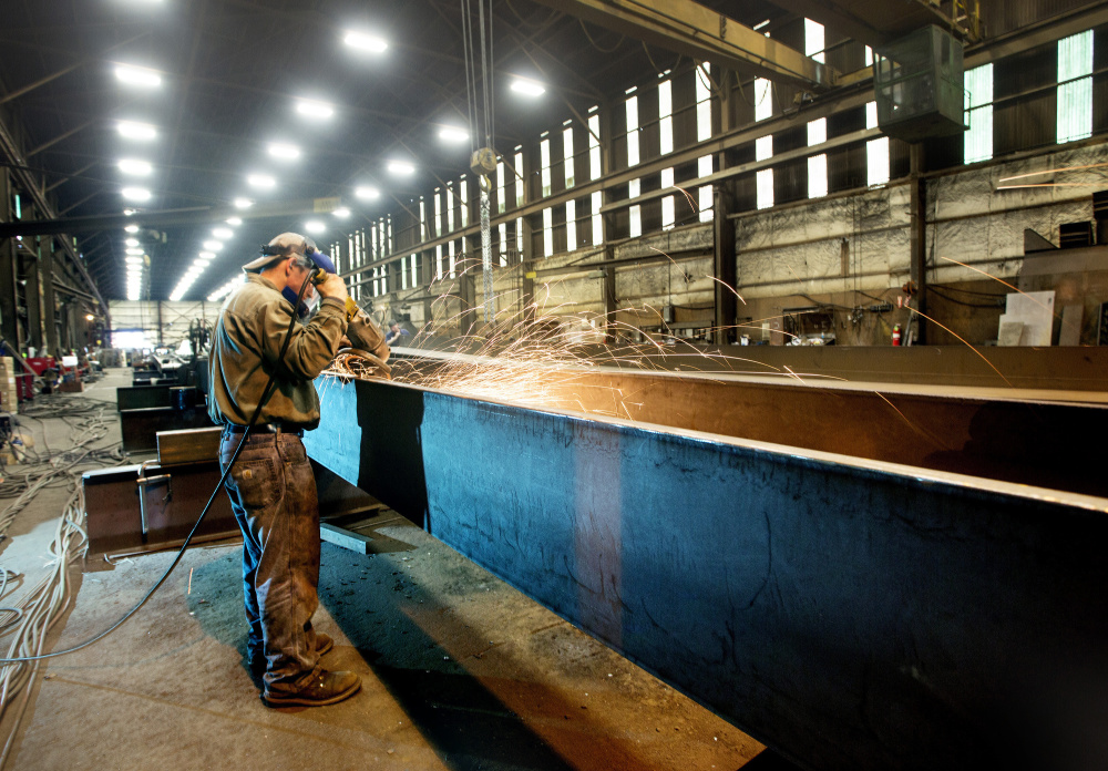 Casco Bay Steel employee Dustin Ford grinds a steel girder that will be used on a project in New Haven, Vt..